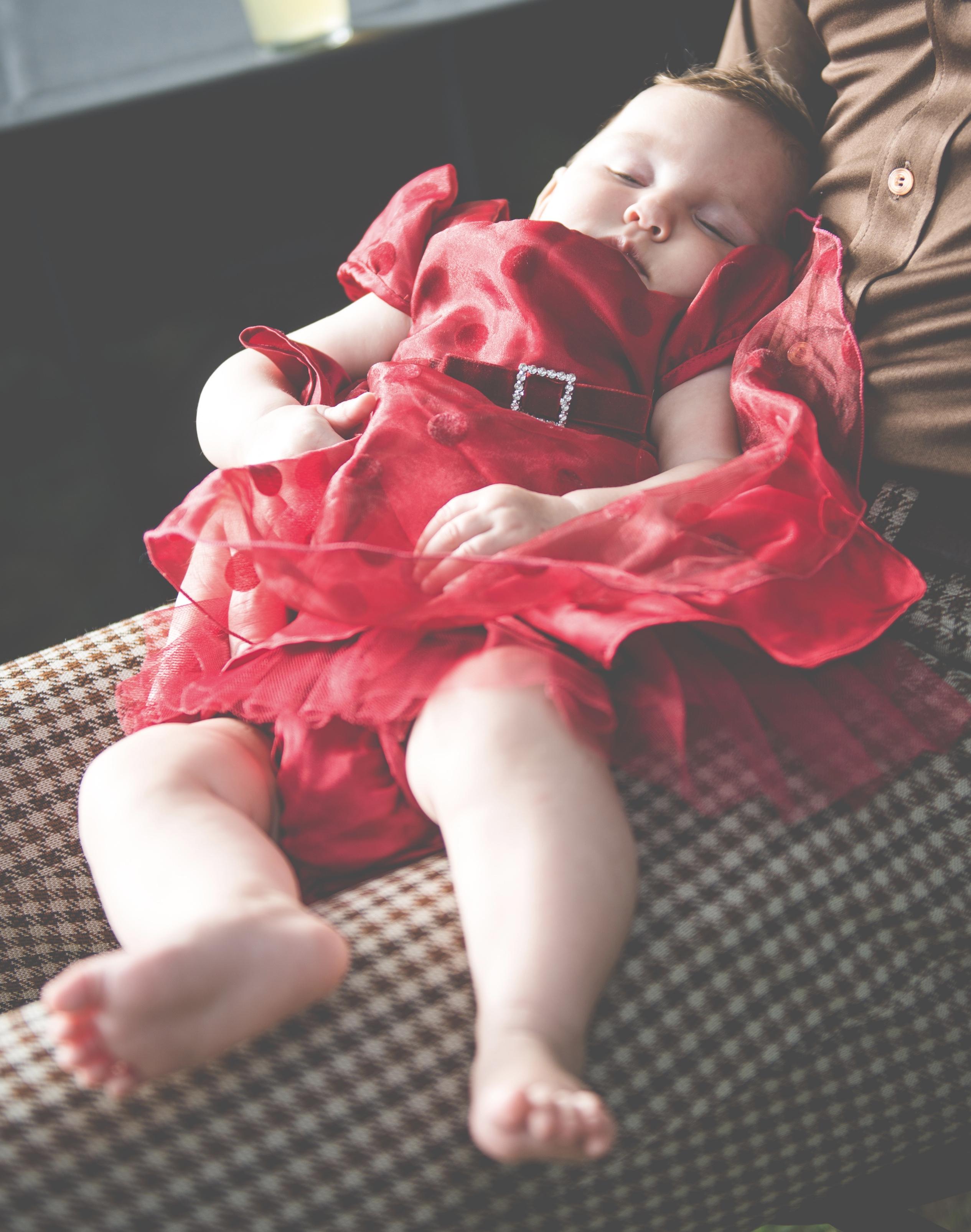Sleeping baby on parent's lap.