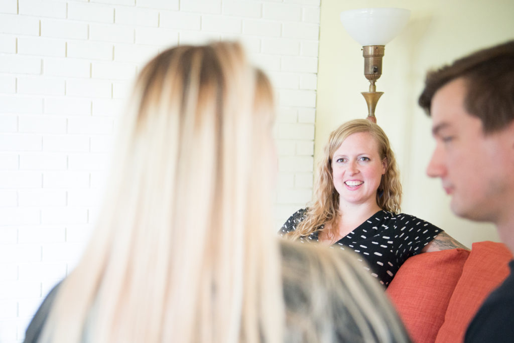 Close up of Allie Machen meeting with a pregnant woman and her partner.