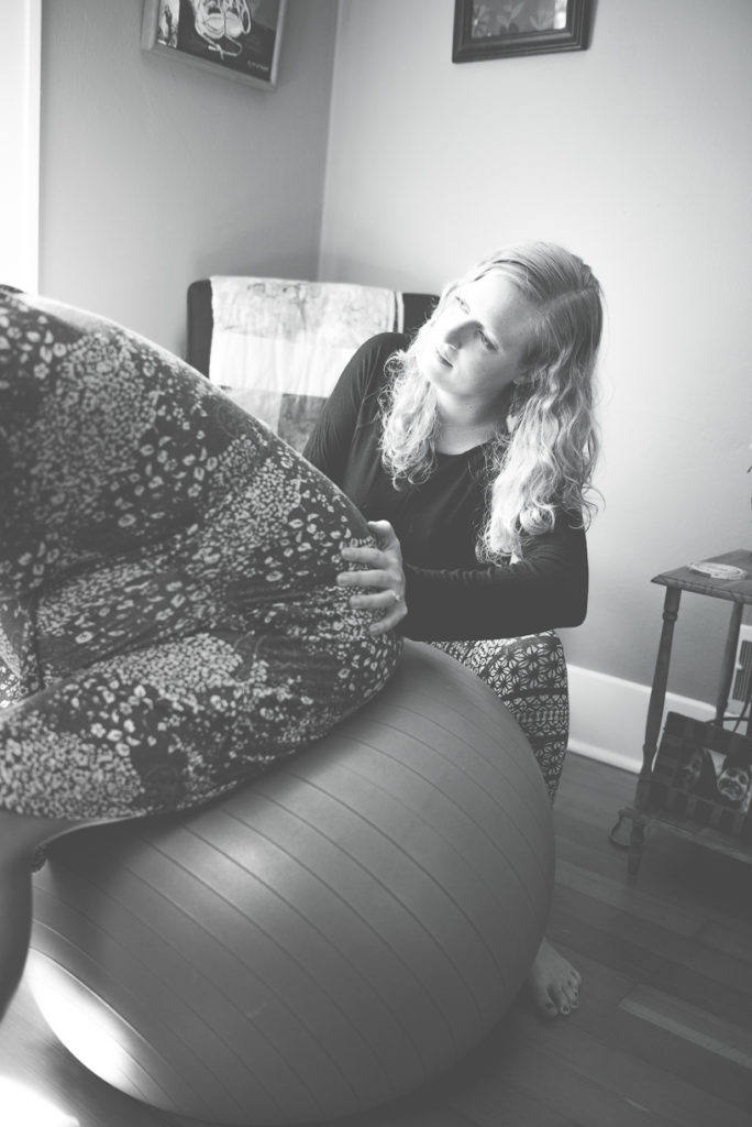Close up Allie Machen performing a doula service by rubbing the back of her pregnant patient who is sitting on an exercise ball.