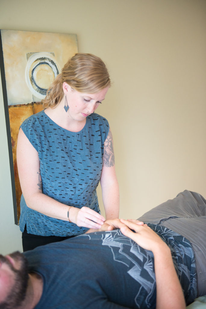 Allie Machen placing acupuncture needles into the hands of her male patient.