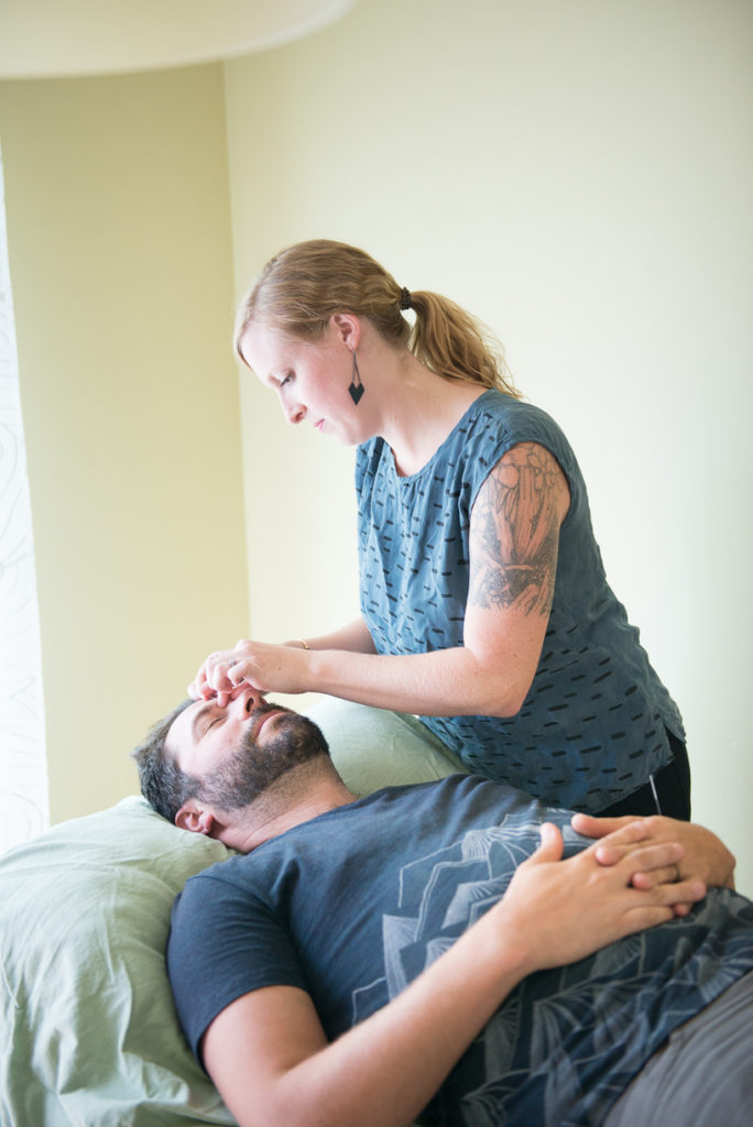 Allie Machen placing acupuncture needles into the face of her male patient.