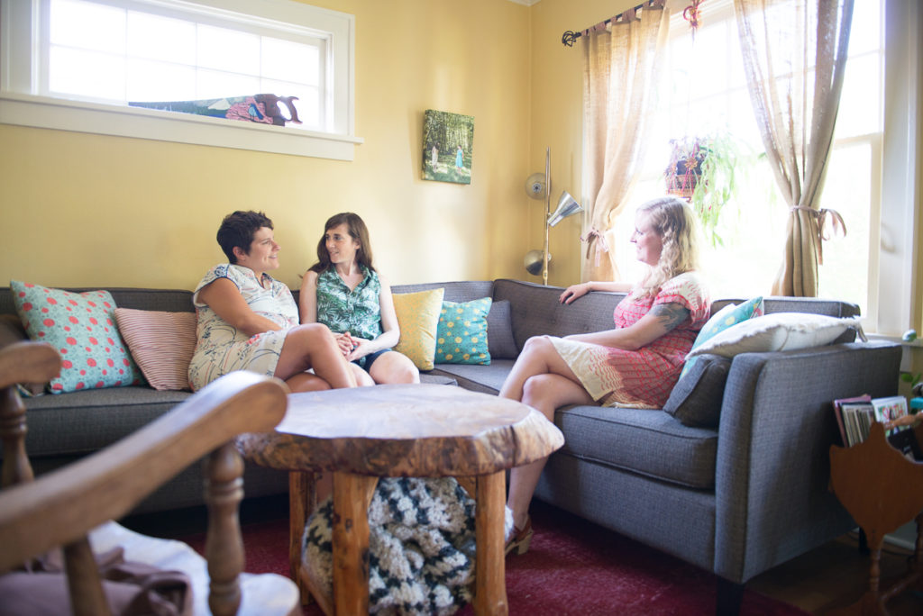 Allie Machen sitting in the living room with her pregnant client and her wife on the couch.
