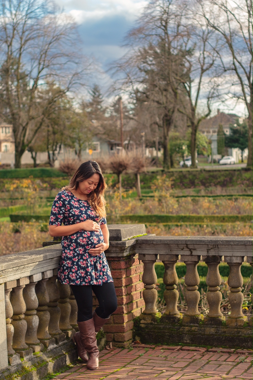 Pregnant woman holding and looking at her pregnant belly, wearing a flower-covered dress, in the rose garden in North Portland, Oregon.